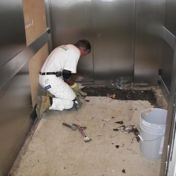 Hand-grinding elevator floor in prep for resinous surface.